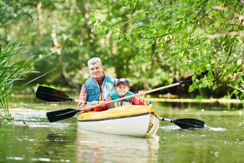 Kayaking no rio na família da floresta na canoa Recreação e férias ativas imagem de stock royalty free