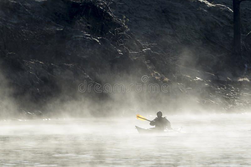 Kayaking przez mgły blisko brzeg fotografia royalty free