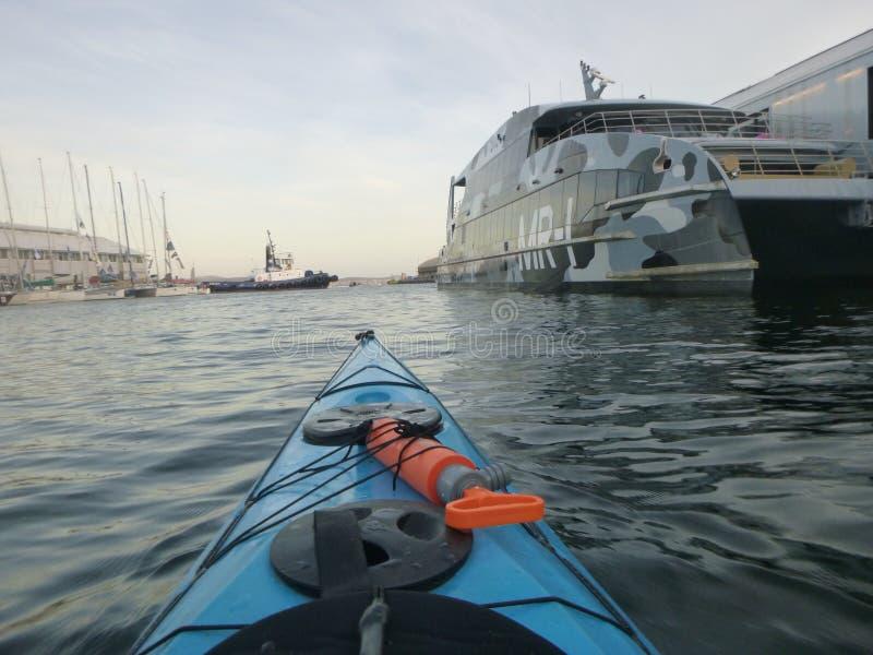 Kayaking runt om yachterna arkivfoto