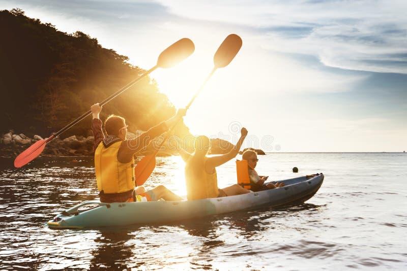 Kayaking solnedgånghav för lycklig familj royaltyfri foto