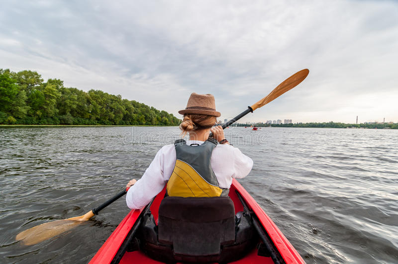 Kayaking travel. Young lady paddling the red kayak. Back view. Holiday and summer adventure stock image