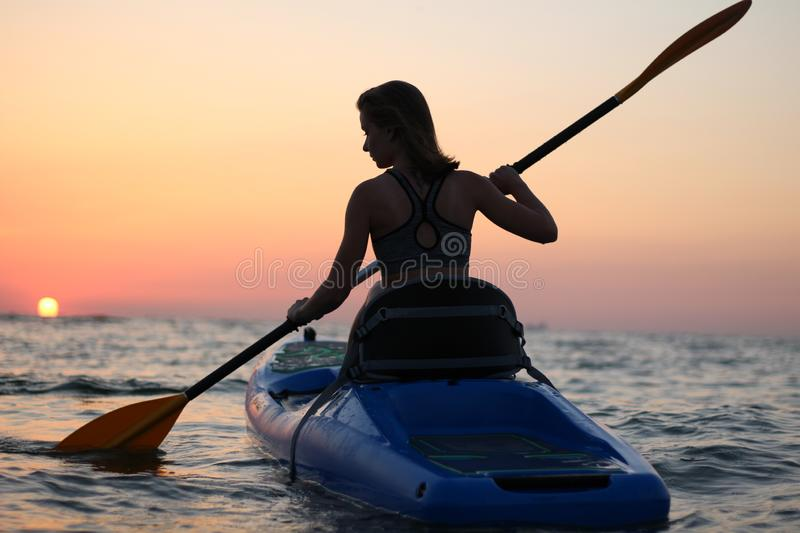 Young girl on the kayak greets the dawn of the sun royalty free stock photo