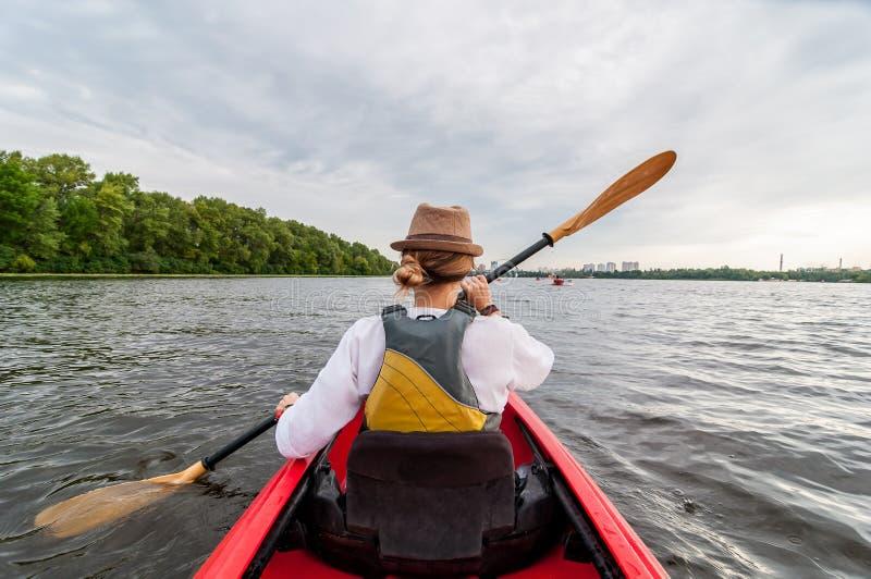 Kayakingsreis Jonge dame die de rode kajak paddelen Achter mening Vakantie en de zomeravontuur stock afbeelding