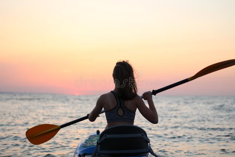 Kayakingsvrouw in kajak Meisje die in het water van een kalme overzees roeien stock fotografie