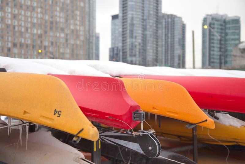 Kayaks colorés stockés pour l'hiver images stock