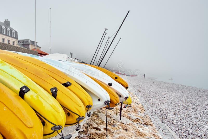 Kayaks jaunes sur un Pebble Beach rocheux pendant le début de la matinée avec la brume brumeuse sur le fond photo stock