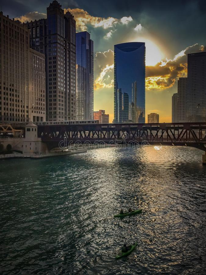 Kayaks provide recreational activities to tourists as the Chicago River reflections of sunset and buildings as sun sets. Sun begins to set over the Chicago River stock photos