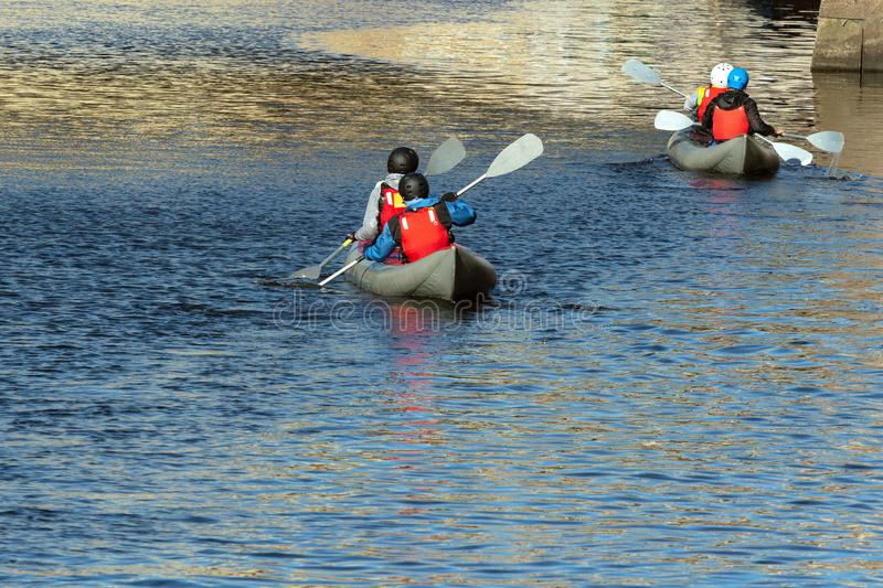 Kayaks on the river. A group of young people canoeing on a city river stock photography
