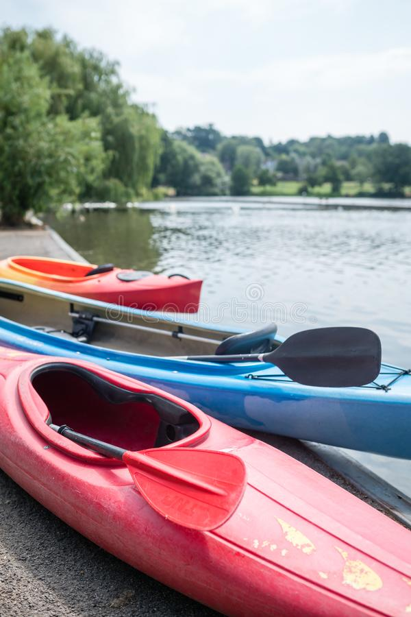 Kayaks on the shore. Three kayaks on the shore of a small lake in summer in Wimbledon Park in London royalty free stock photos