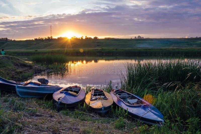 Kayaks sur la berge Beau coucher du soleil sur la rivière photo libre de droits