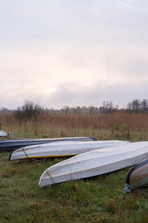 Kayaks of water tourists during a halt in the camp. Sunrise over morning swampy meadow surrounded by dry reed. Nature of Volyn royalty free stock images
