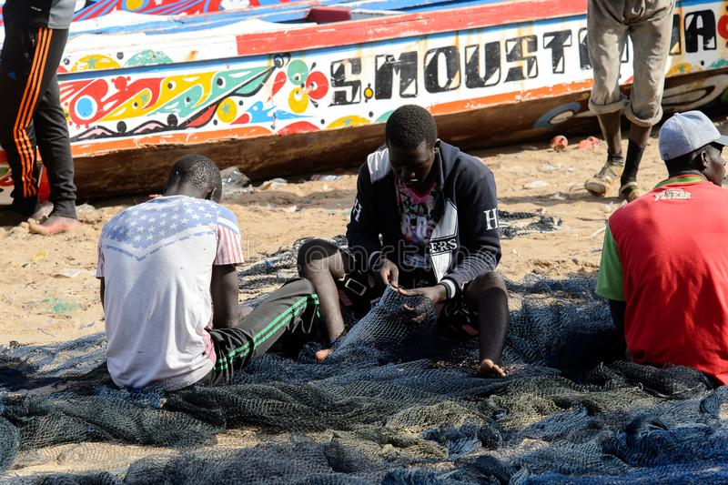Unidentified Senegalese man sews a fishing net on the coast of stock photos