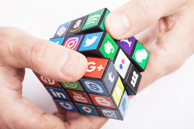 KAZÁN, RUSIA - 27 de enero de 2018: La mano del hombre sostiene un cubo con la colección de logotipos sociales populares de los m imagen de archivo libre de regalías