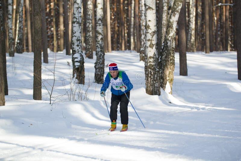 KAZÁN, RUSIA - marzo de 2018: maratón corriente del esquí del viejo hombre en bosque congelado soleado foto de archivo libre de regalías