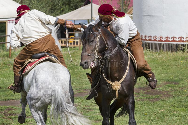 Kazach mężczyzna robią tradycyjnemu koczowniczemu ręki zapaśnictwu na ich koniu w Kazachstan, zdjęcie stock