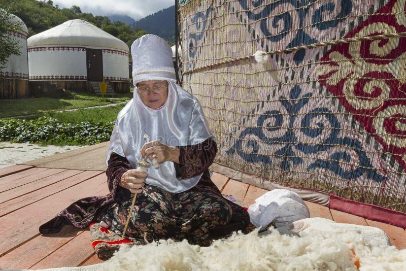 Kazach starsza dama w lokalnej koczowniczej sukni wiruje wełnę fotografia royalty free