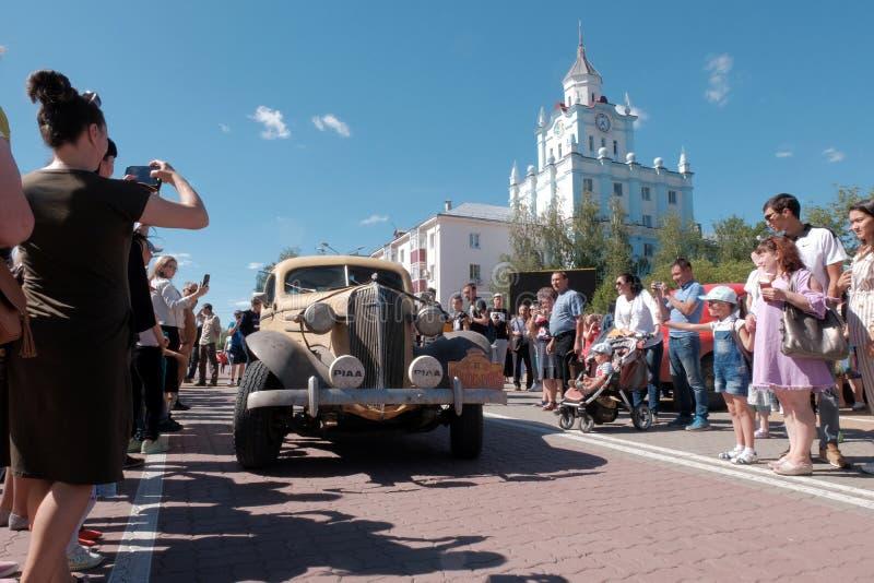 Kazachstan, Kostanay, 19-06-19, Ingezetenen van de stad ontmoet een oude auto op de straat Een meisje fotografeert het uitstekend stock foto's