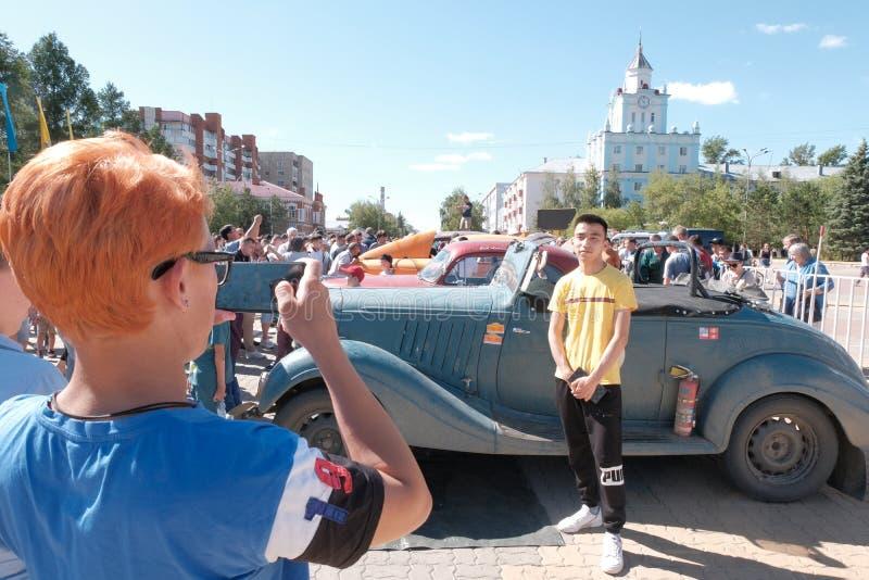 Kazachstan, Kostanay, 19-06-19 Wielka automobilizm przygoda - Peking Paryż Miedzianowłosa dziewczyna bierze obrazki Azjatycki męż obraz stock