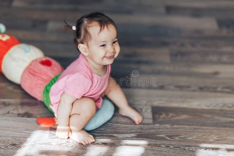 Kazakh caucasiano asiático brincalhão da raça misturada da menina do bebê de um ano e menina alemão no fundo amarelo fotos de stock royalty free