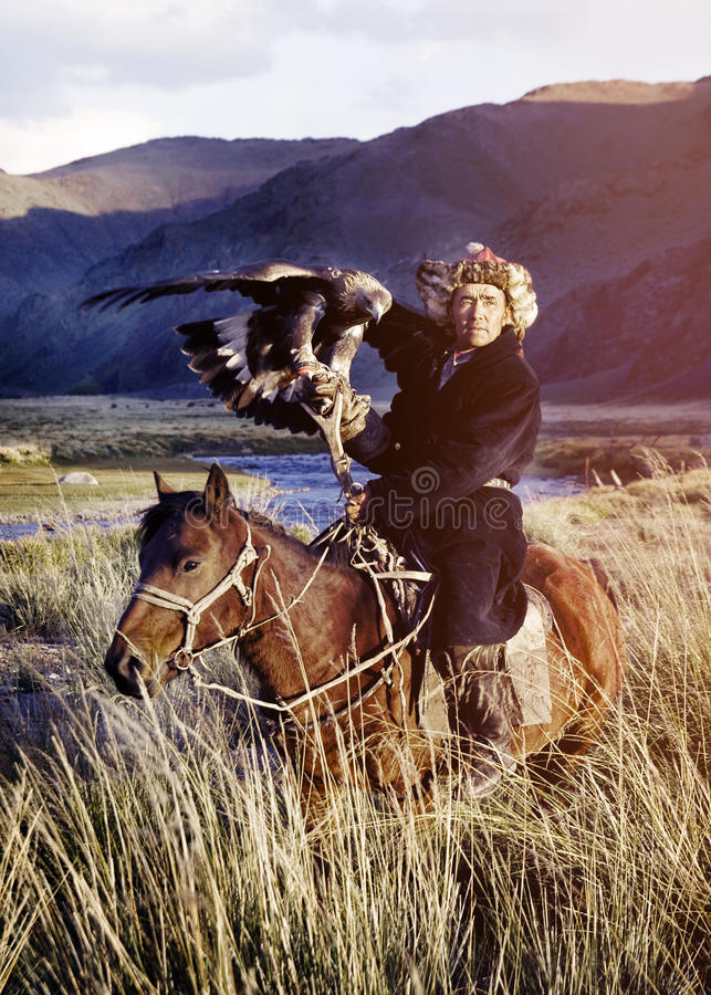 Kazakh en caballo con Eagle Catching Concept imagenes de archivo