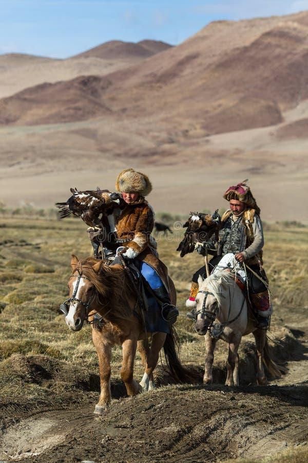 KazakhEagle Hunters traditionella kläder, medan jaga till den haren rymma guld- örnar på hans armar i ökenberg royaltyfria foton