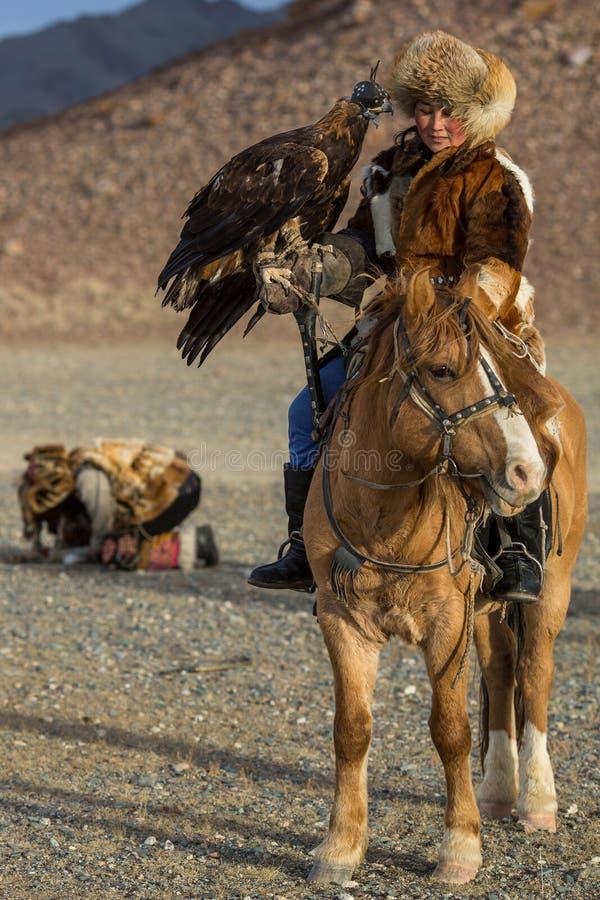 KazakhkvinnaEagle Hunter traditionella kläder, medan jaga till haren som rymmer en guld- örn på hans arm royaltyfri bild