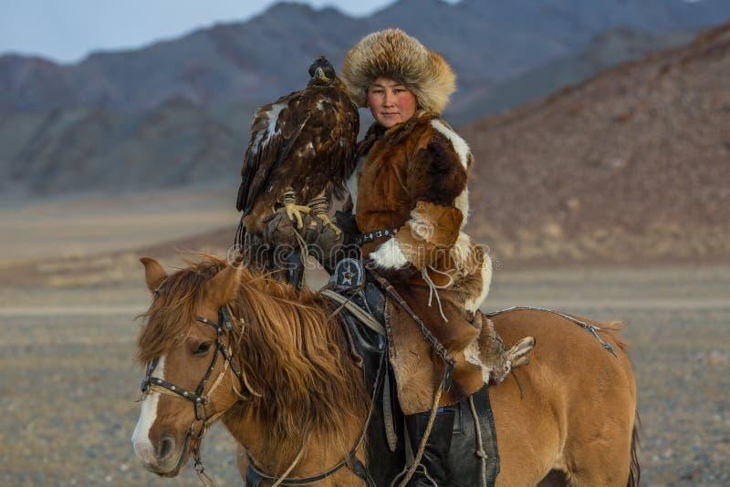 KazakhkvinnaEagle Hunter traditionella kläder, medan jaga till haren som rymmer en guld- örn på hans arm arkivfoto