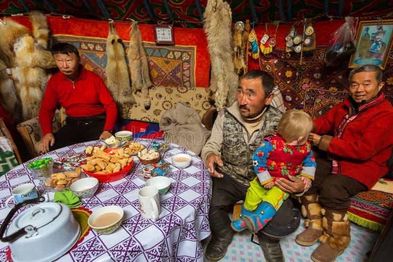 Kazakhsfamilj av jägare med att jaga den deras insidan för guld- örnar mongolianen Yurts royaltyfri foto
