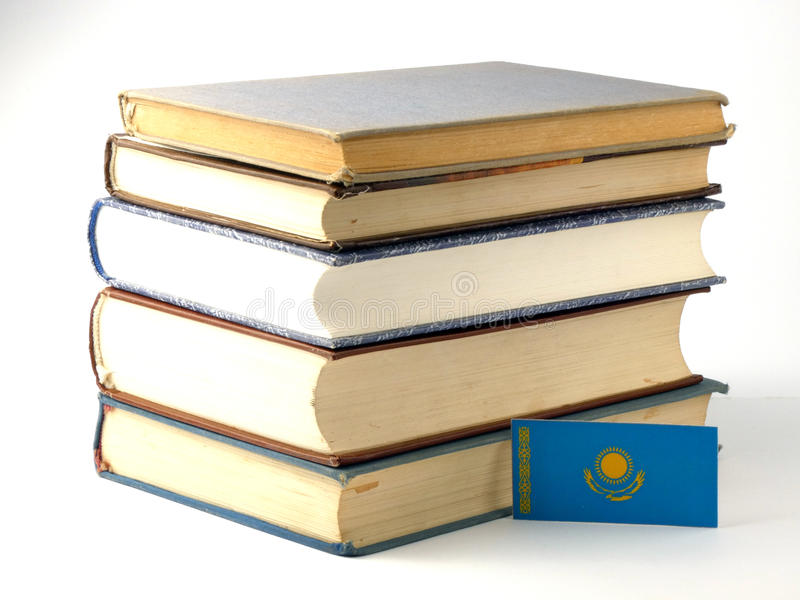 Kazakhstan flag with pile of books on white background royalty free stock photo