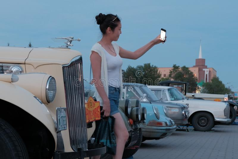 Kazakhstan, Kostanay, 19-06-19, The Greatest Motoring Adventure - Peking to Paris. Asian girl in shorts makes a selfie on the. Kazakhstan, Kostanay, 19-06-19 stock photography