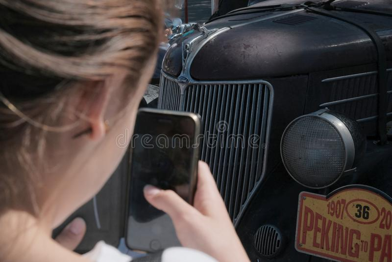 Kazakhstan, Kostanay, 19-06-19, The Greatest Motoring Adventure - Peking to Paris. A girl photographs a vintage Ford car using a stock photos