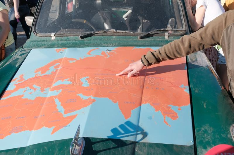 Kazakhstan, Kostanay, 19-06-19, Map of Eurasia on the hood of an old car. The hand of the guy indicates the path of movement of. The rally participants. The royalty free stock image