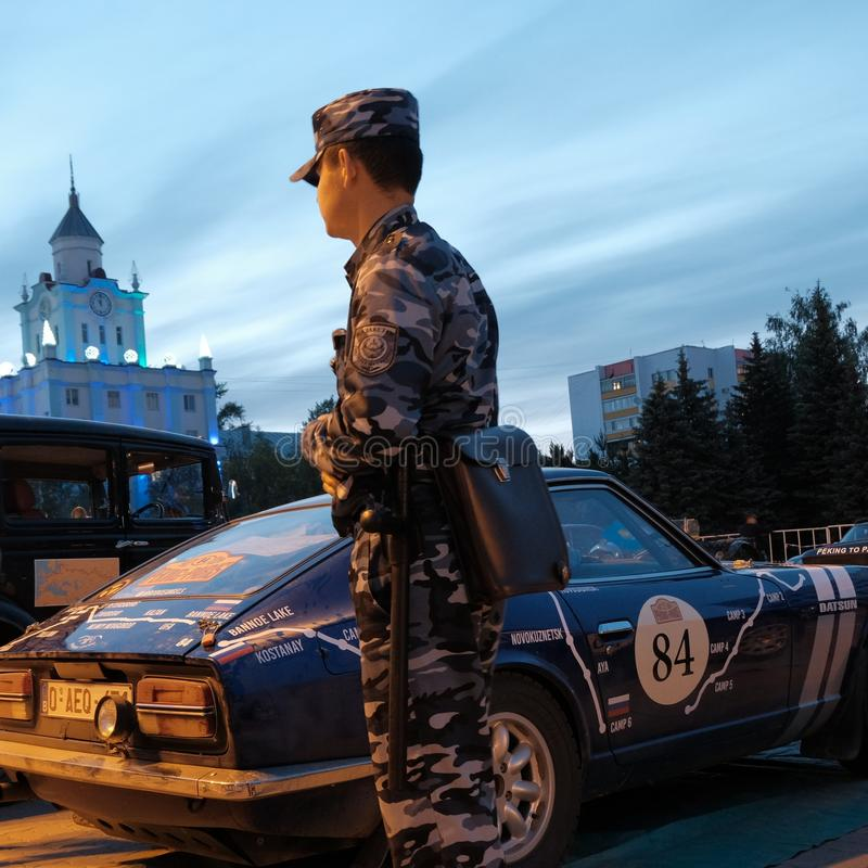 Kazakhstan, Kostanay, 19-06-19, A policeman near a vintage car on the background of the city tower. The Greatest Motoring. Kazakhstan, Kostanay, 19-06-19, A stock photo