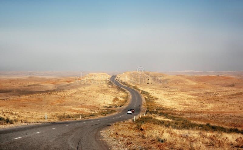 Kazakistan: auto in viaggio per una strada deserta attraverso una steppa fotografia stock