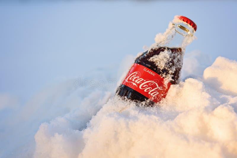 Kazan, Rosja, Marzec, 17, 2018: Oryginalna szklana butelka marznąca koka-kola wtykał w śniegu w jaskrawym zmierzchu fotografia royalty free