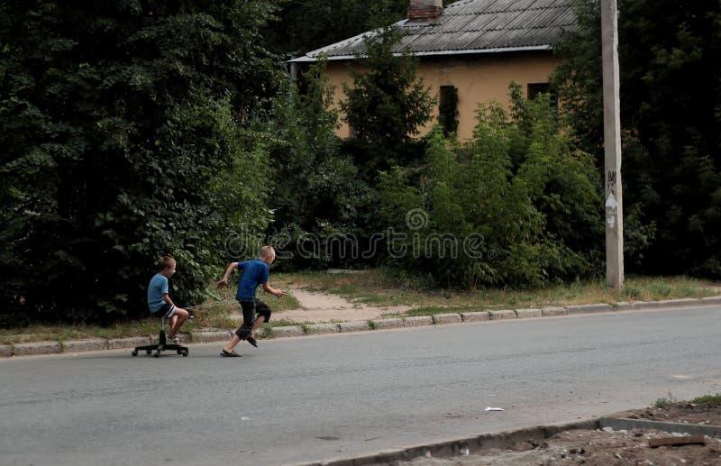 Kazan, Rusland, 14 augustus 2011, Russische slechte wezenspelen met gebroken stoel stock afbeeldingen
