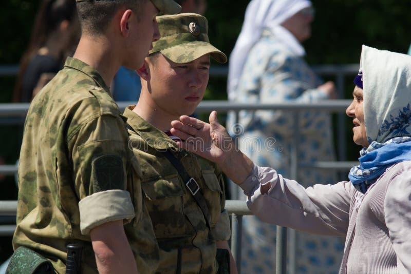 KAZAN, RUSLAND - JUNI 23, 2018: Traditioneel Tatar festival Sabantuy - Leuke oude vrouw in een sjaal die aan jonge militairen spr stock foto's
