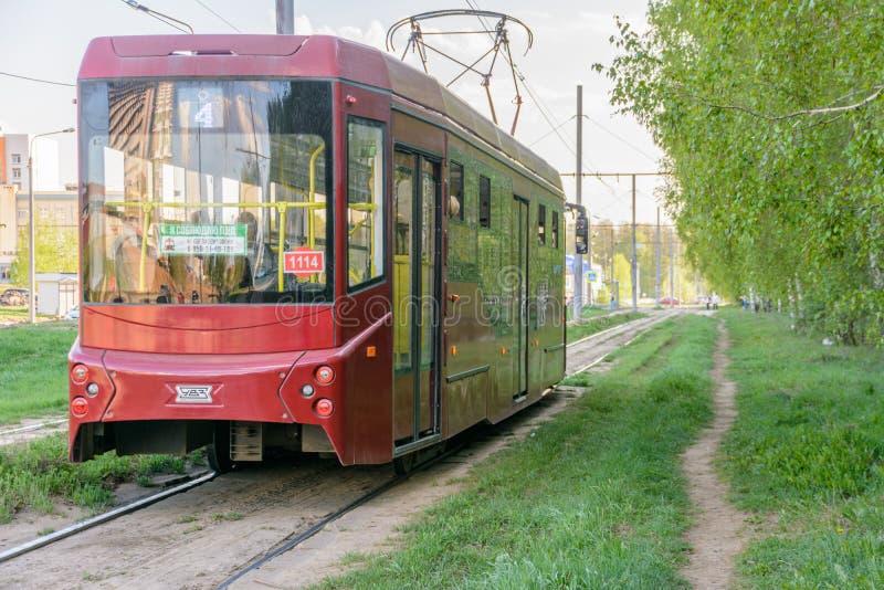 Kazan, Rusland - Mei 9, 2019: Een tram geeft een zonnige de lentedag dichtbij het voetpad door Elektrisch en ecologisch vervoer stock afbeelding