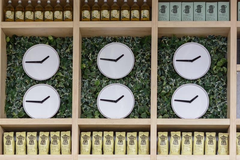 Kazan/Rusland - Mei 10, 2019: Winkelvenster met interessante horloges, stroop en pakketten met koffie Heel wat klok, heel wat tij stock foto's