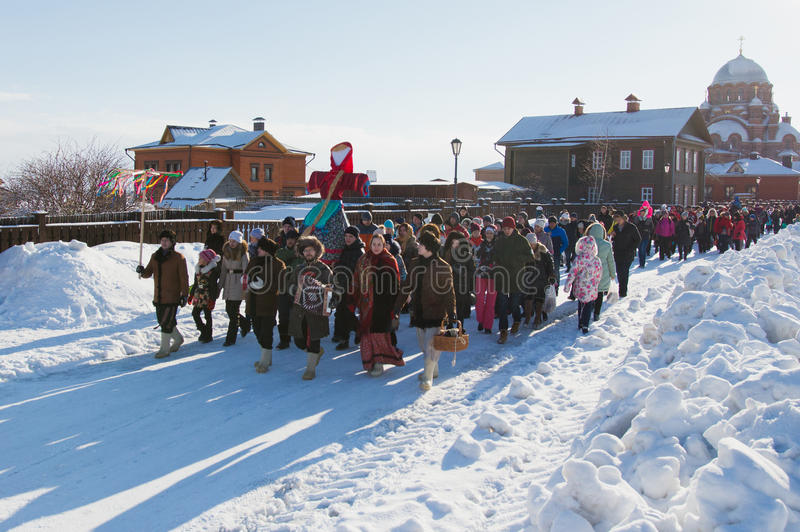 Kazan, Russia - 28 february 2017 - Sviyazhsk Island : Russian ethnic carnival Maslenitsa - A crowd of people walking. Along the snowy road and carrying a stock image