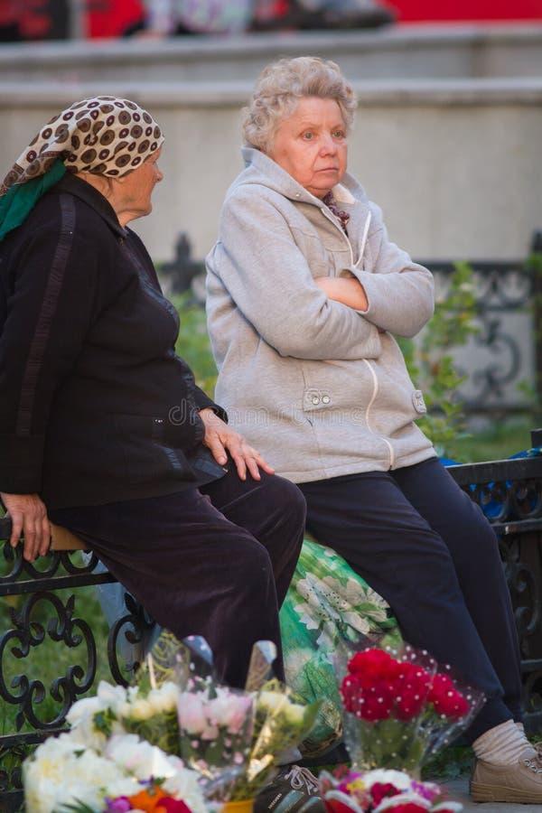 KAZAN, RUSSIA - 21 GIUGNO 2018: Le donne anziane tristi che si siedono sul recinto alla sera dell'estate vende i fiori immagine stock libera da diritti