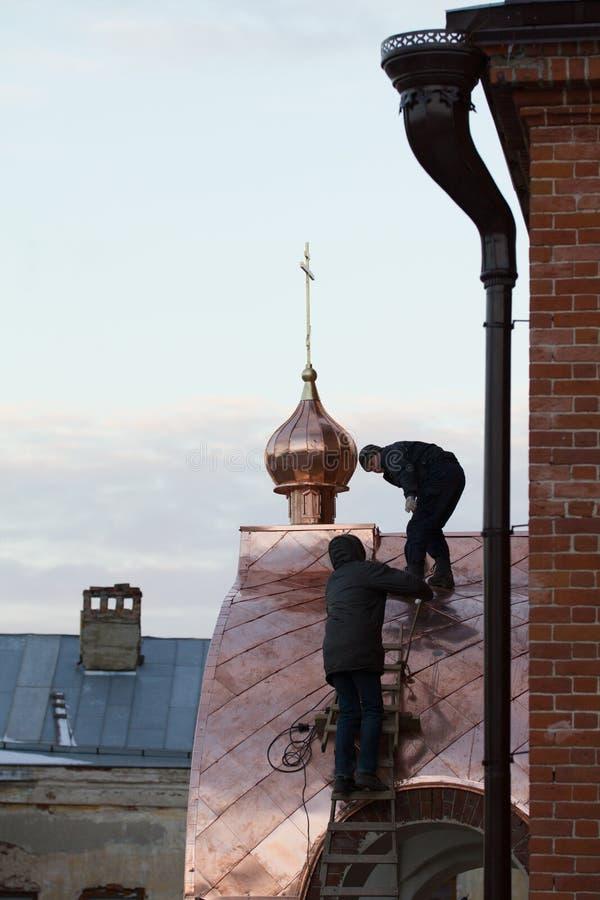 KAZAN, RUSSIA, il 19 novembre 2016, un Roofer di due lavoratori che ripara tetto di vecchia chiesa del ` dei credenti del ortodox fotografia stock libera da diritti