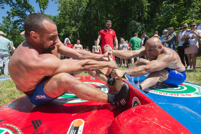 KAZAN, RUSSIA - JUNE 23, 2018: Traditional Tatar festival Sabantuy - Strong men wrestling outdoors at summer day. Close up stock image