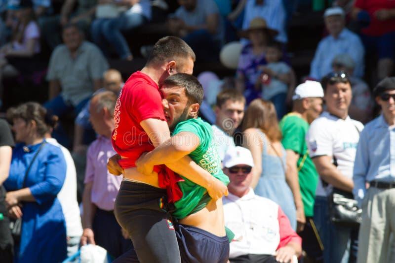 KAZAN, RUSSIA - JUNE 23, 2018: Traditional Tatar festival Sabantuy - Two fighters wrestling in folk kuresh battle. Outdoors, close up royalty free stock photo