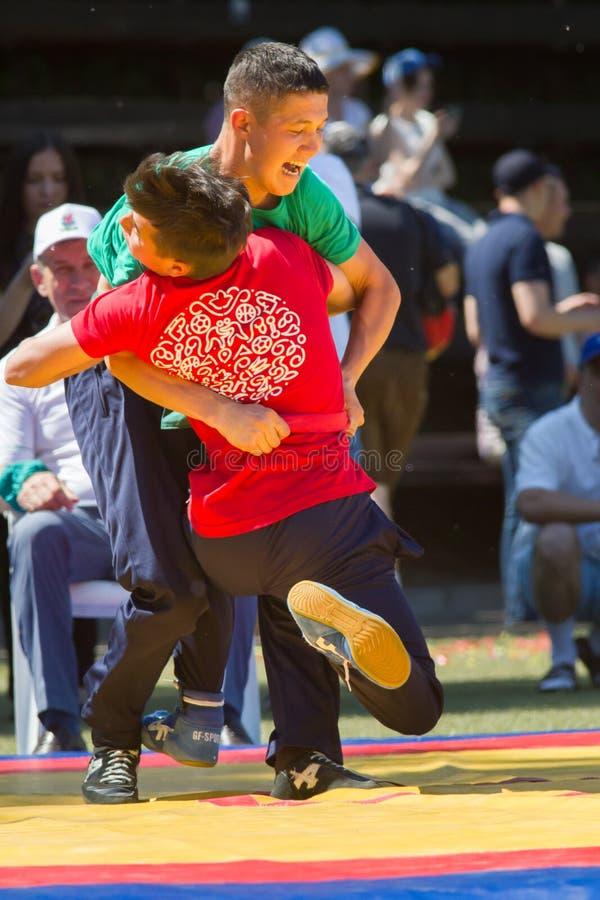 KAZAN, RUSSIA - JUNE 23, 2018: Traditional Tatar festival Sabantuy - Two male teenagers fighting in folk wrestling. Kuresh, close up royalty free stock photography