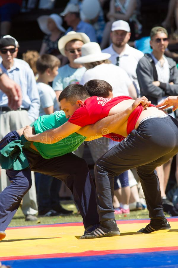 KAZAN, RUSSIA - JUNE 23, 2018: Traditional Tatar festival Sabantuy - Two young men fighting in folk wrestling kuresh. Outdoors, close up stock photos