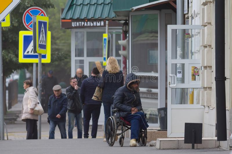 KAZAN, RUSSIA - September 9, 2017: Disabled beggar poor man with wheelchair on the Ostrovskogo street asking for money royalty free stock photo