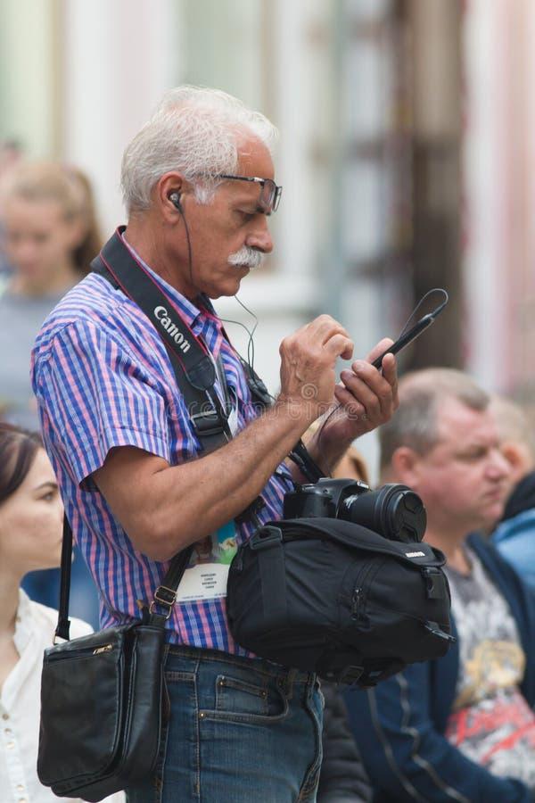 KAZAN RYSSLAND - JUNI 21, 2018: Använder det yrkesmässiga fotografanseendet för mogen man på den Bauman gatan och en smartphone royaltyfri bild