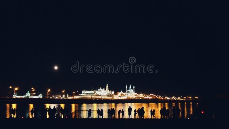 Kazan Ryssland, 12 kan 2017 - Kazan kremlin med reflexion i floden på natten med konturer av folk royaltyfria bilder