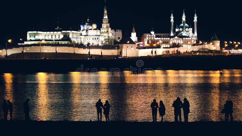 Kazan Ryssland, 12 kan 2017 - Kazan kremlin med reflexion i floden på natten och konturer av folk arkivbilder